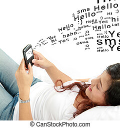 woman texting on phone lying on bed - Pretty woman texting...