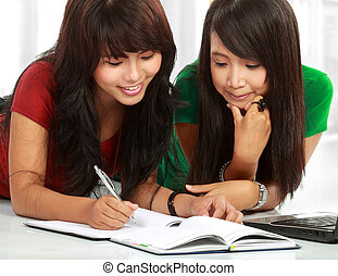 two young asian student studying - young asian student lying...
