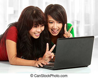 woman chatting on laptop - Two pretty women having a online...