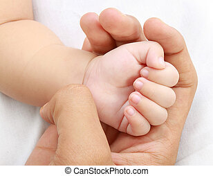 little baby hand with mothers hand