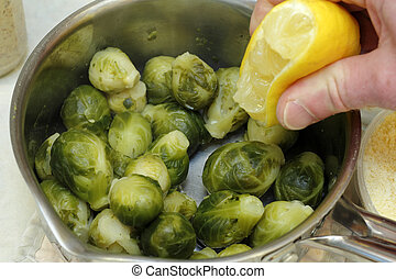 Flavoring Brussels Sprouts - Hand squeezing lemon juice from...