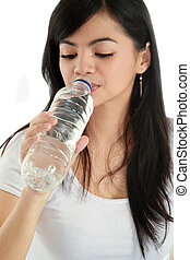 Woman drinking water from bottle, isolated on white...