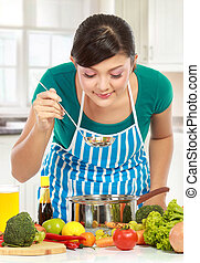 cooking delicious food - beautiful young women cooking and...