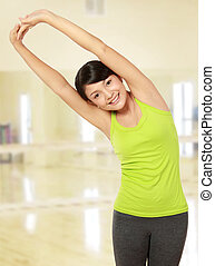 warming up - healthy fitness woman stretching in the gym