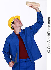 young bricklayer in jumpsuit inspecting brick