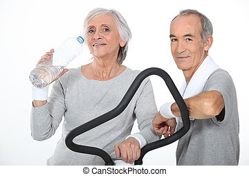 Elderly couple working out together in gym