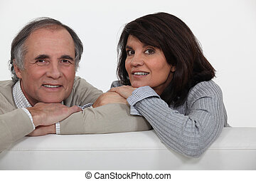 A middle age couple on their sofa.