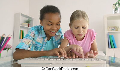 Playful typing - Cute little girls typing playfully on the...