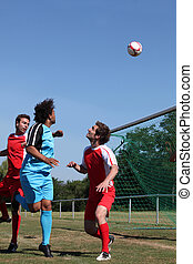Footballer heading ball towards goal