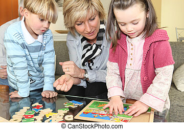 Woman and children with a wooden puzzle