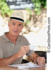 65 years old man wearing a straw hat and drinking a tea cup...