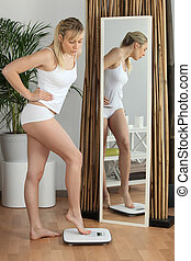 Blond woman weighing herself