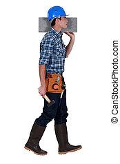 Tradesman carrying a cinder block