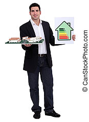 man holding an architectural model and an energy consumption...