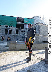 young bricklayer standing in construction site