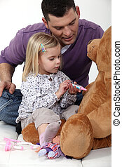 Man with little girl playing with teddy bear