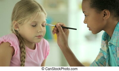 Teen beautician - Girls applying eye-shadows and lipstick to...