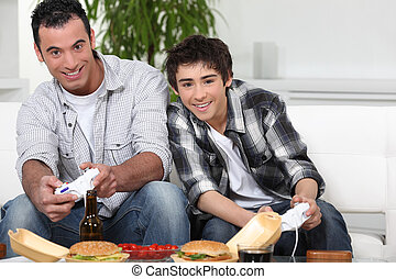 Father and son playing video games whilst eating fast-food