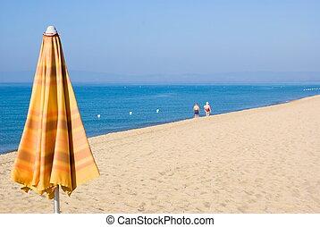 Beach umbrella closed on the beach and rescue boat