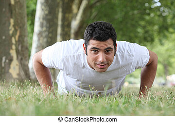 Man doing press ups in the park