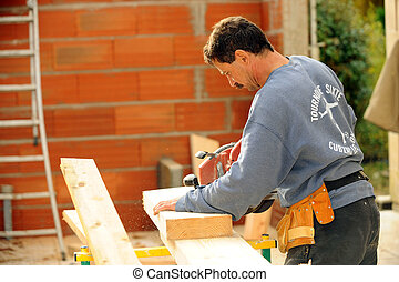 Manual worker using circular saw on site