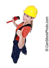 Tradeswoman giving the thumbs up and holding a pipe wrench