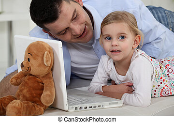 Little girl in front of computer with her dad