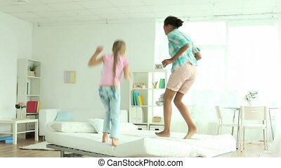Bed test - Preteen girls jumping cheerfully on the bed