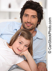 Father and daughter relaxing on a sofa