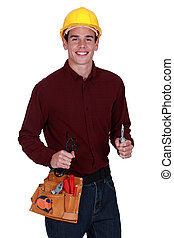 Tradesman holding a pair of pliers and a cable