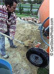 Man shovelling gravel into a mixer