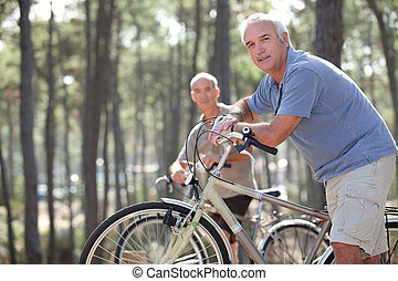two seniors riding bikes in the park