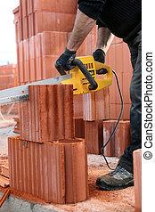 Builder cutting bricks to size