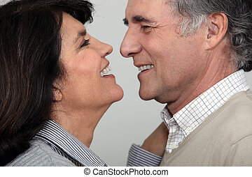 A middle age couple about to kiss.