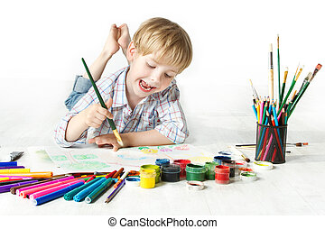 Happy cheerful child drawing with brush in album using a lot of painting tools. Creativity concept.