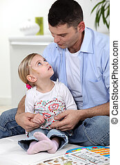 Father and daughter at home reading