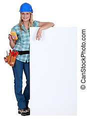Female electrician standing with advertising board