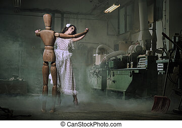 A beautiful woman dances with a wooden dummy