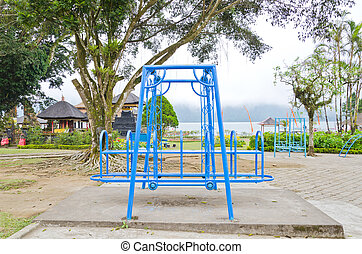 swing set on the playground front of foggy lake