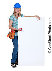 Female construction worker with a blank board