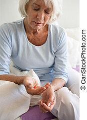 Elderly woman taking a pill
