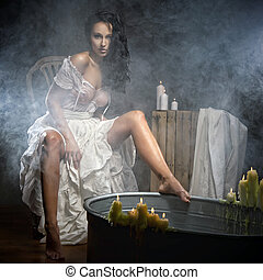 Woman relaxing in bath with candels