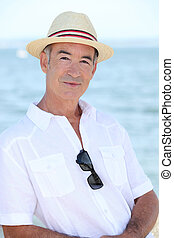 Senior man in a straw hat standing by the water