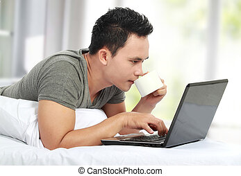 man lying on a bed and using a laptop computer - A young man...