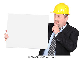 Man in hard hat holding blank message board