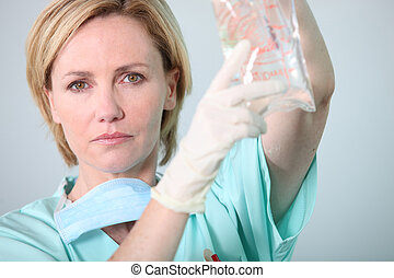 Hospital nurse attending to a drip bag
