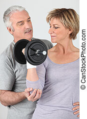 Man helping a woman lift a dumbbell