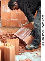 Mason chipping at bricks