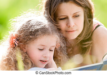 beautiful little girl reading book with ger mother -...