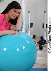 Woman leaning on gym ball